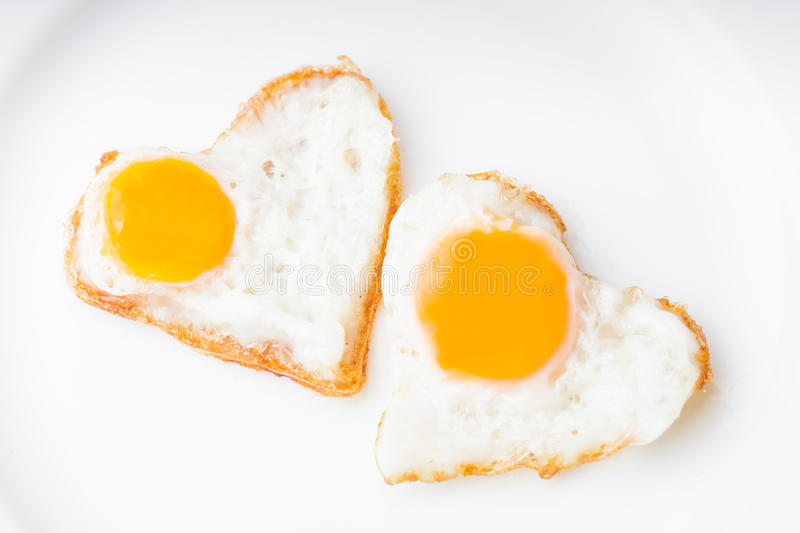 Heart fried eggs. Heart shape fried eggs on the white plate royalty free stock image