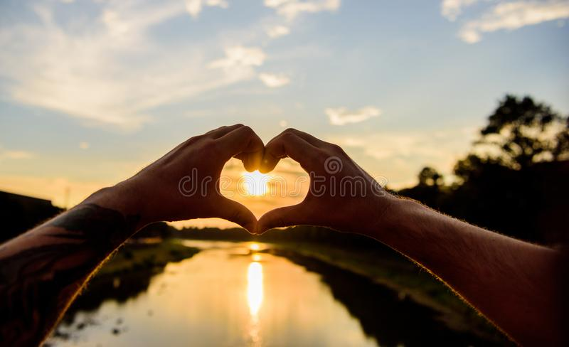 Heart gesture in front of sunset above river water surface, defocused. Top places for romantic date. Male hands in heart. Shape gesture symbol of love and royalty free stock image