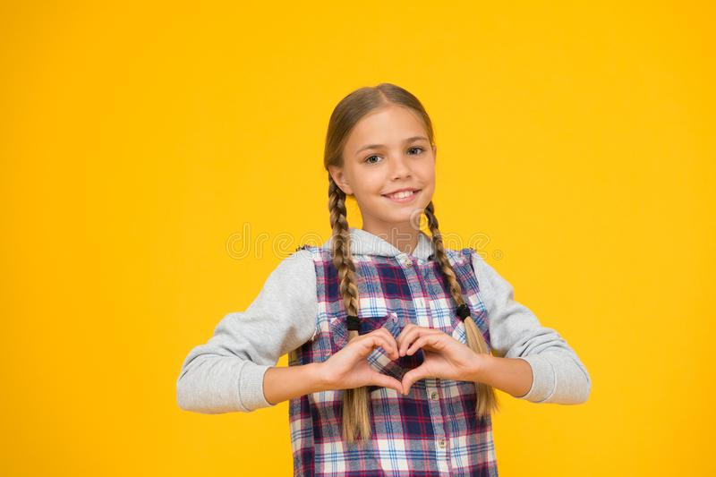 Heart gesture. Happy international childrens day. Little girl yellow background. Good mood concept. Positive vibes. Sincere emotions. Cute braided girl. Kid royalty free stock images