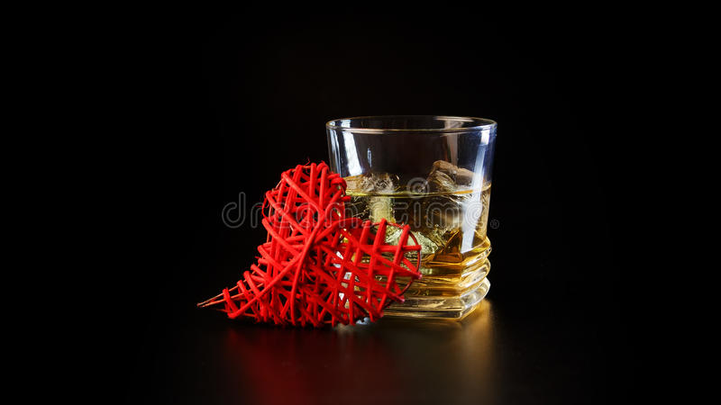 Heart and glass of alcohol on black table royalty free stock photography