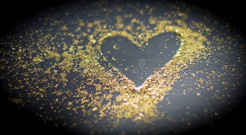 Heart in golden powder stock photos