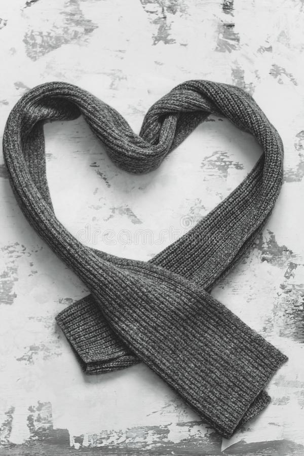 Heart grey knitted scarf. On a grey background stock photography
