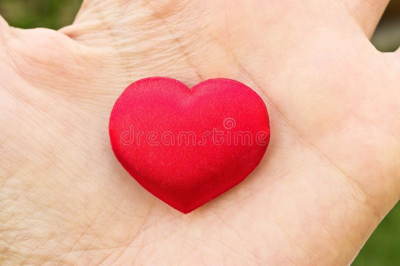 Heart in hand. Romantic concept. Big red heart in woman´s open palm. Symbol of love to everybody royalty free stock photo