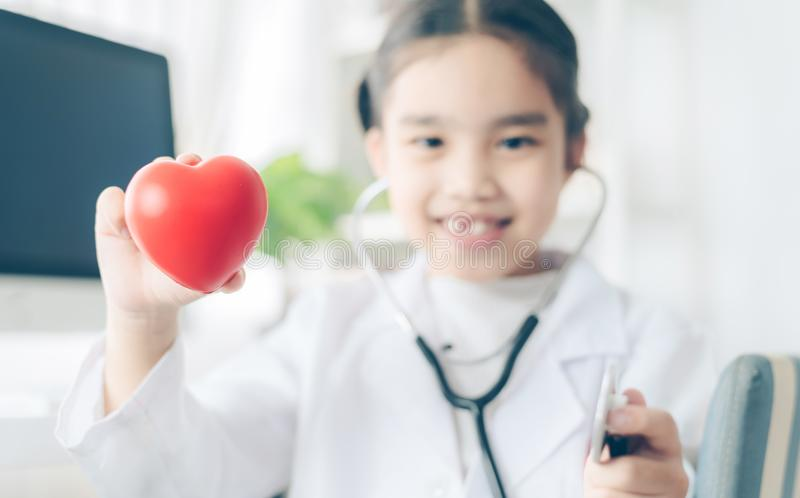 Heart in the hands of the Cute child in doctor coat with stethoscope . Love concept. Health concept royalty free stock photography