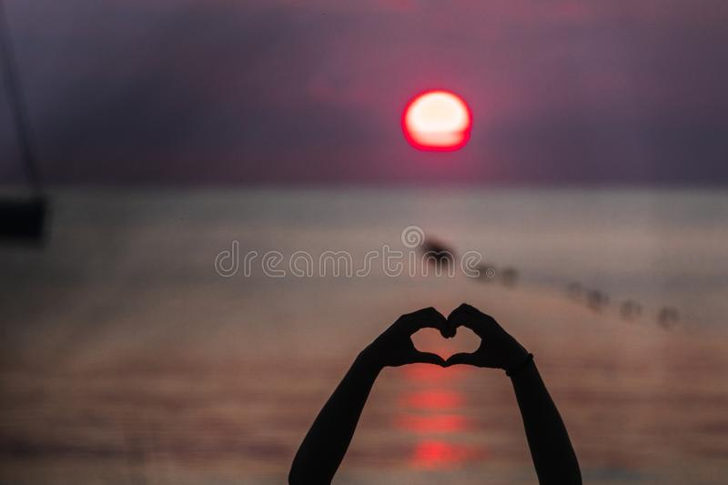 Heart Hands and sea sunset. Shadow of two hands drawing a heart in a Formentera sea sunset stock photos