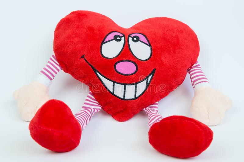 Heart. Happy Valentine`s day. Red smiling plush pillow heart with hands and lags on white background. Close up stock photography