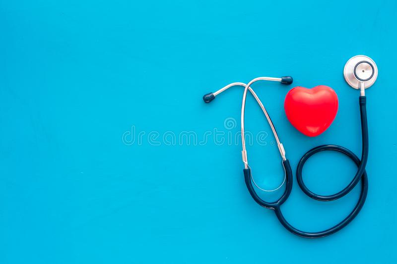 Heart health, health care concept. Stethoscope near rubber heart on blue background top view space for text stock photography