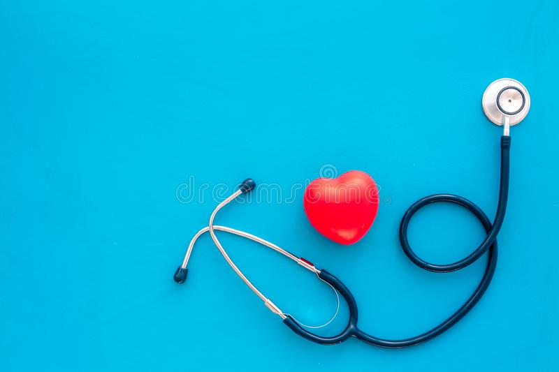 Heart health, health care concept. Stethoscope near rubber heart on blue background top view space for text stock photos