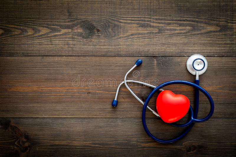 Heart health, health care concept. Stethoscope near rubber heart on dark wooden background top view copy space stock photography