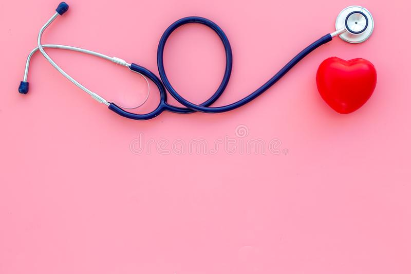 Heart health, health care concept. Stethoscope near rubber heart on pink background top view space for text stock photos