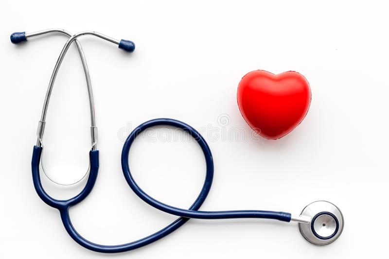 Heart health, health care concept. Stethoscope near rubber heart on white background top view stock image