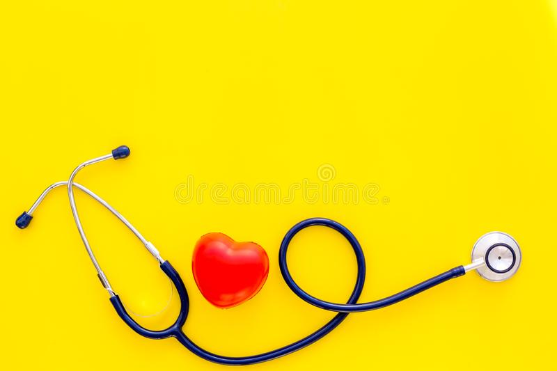 Heart health, health care concept. Stethoscope near rubber heart on yellow background top view copy space royalty free stock photos