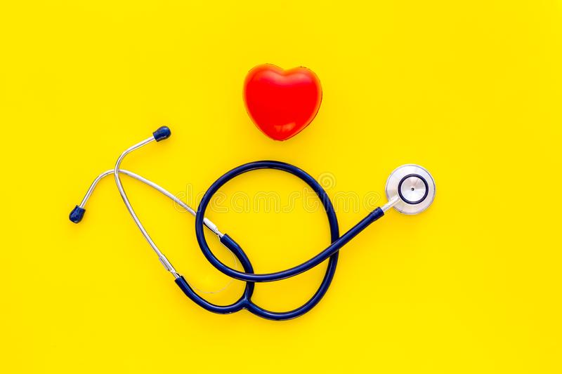 Heart health, health care concept. Stethoscope near rubber heart on yellow background top view copy space royalty free stock images