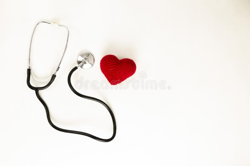 Heart health and prevention concept. Stethoscope and red heart of crochet on white isolated background with space for text stock photography