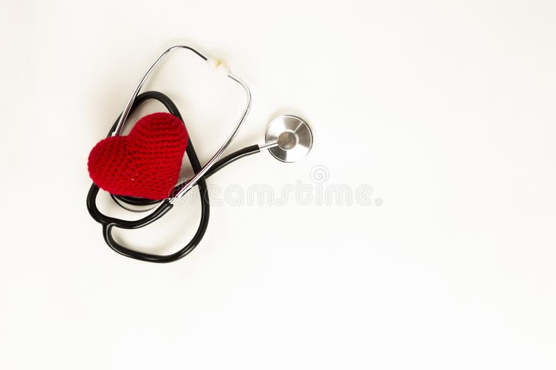 Heart health and prevention concept. Stethoscope and red heart of crochet on white isolated background with space for text.  stock photos