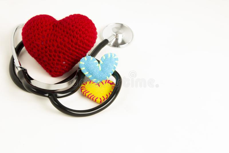 Heart health and prevention concept. Stethoscope and red heart of crochet on white isolated background with space for text.  stock images