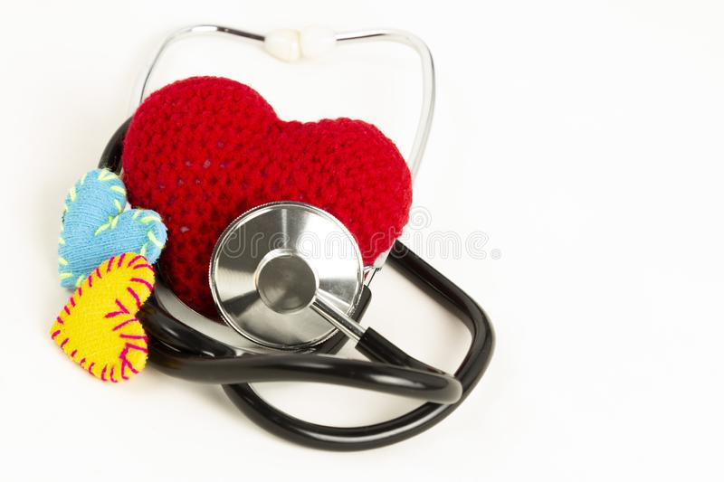 Heart health and prevention concept. Stethoscope and red heart of crochet on white isolated background with space for text royalty free stock images