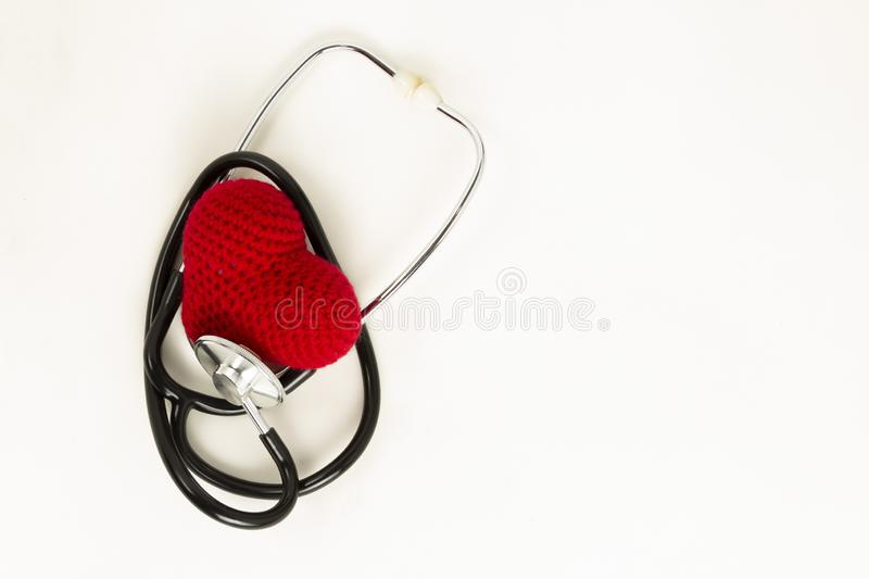 Heart health and prevention concept. Stethoscope and red heart of crochet on white isolated background with space for text royalty free stock photography