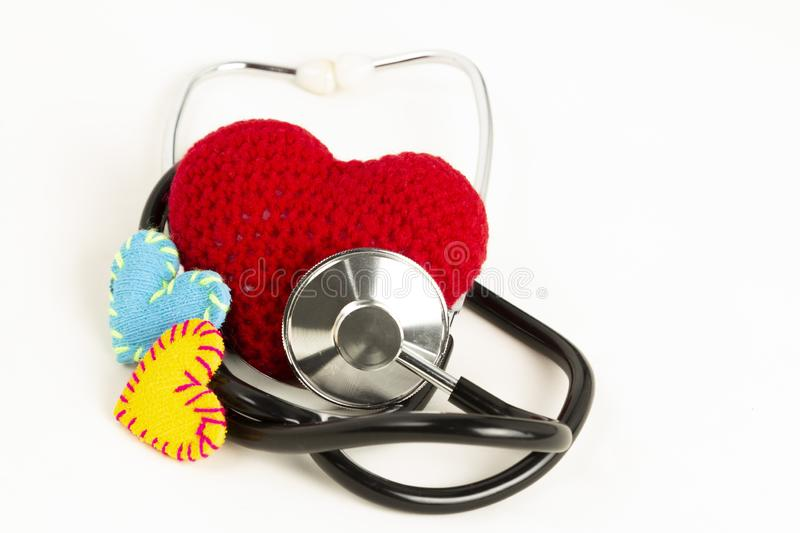 Heart health and prevention concept. Stethoscope and red heart of crochet on white isolated background with space for text royalty free stock photo
