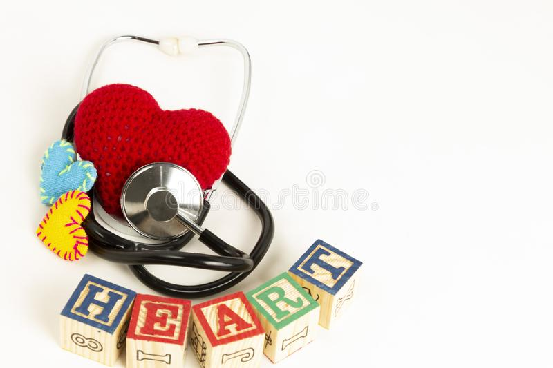 Heart health and prevention concept. Stethoscope and red heart of crochet on white isolated background with space for text stock photos