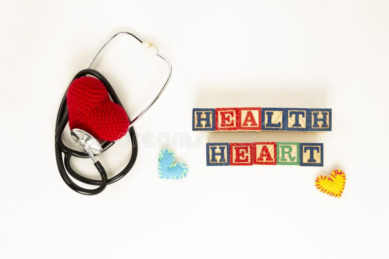 Heart health and prevention concept. Stethoscope and red heart of crochet on white isolated background with space for text royalty free stock photos