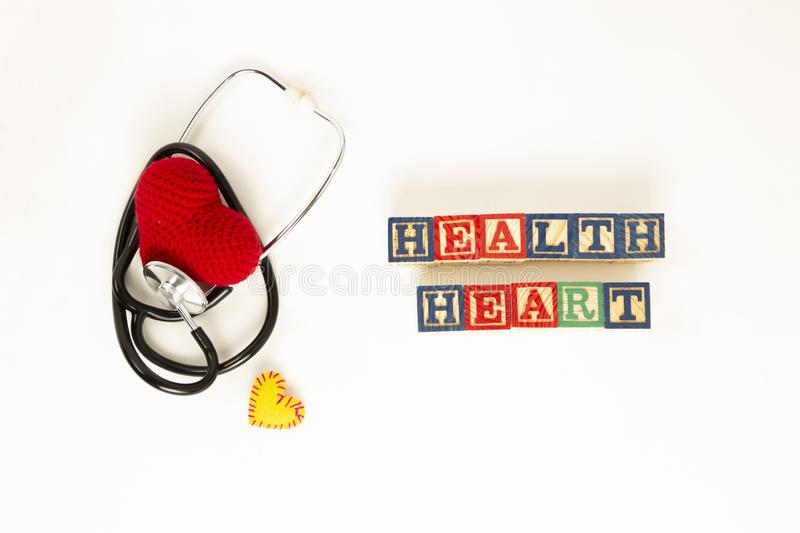 Heart health and prevention concept. Stethoscope and red heart of crochet on white isolated background with space for text stock photo