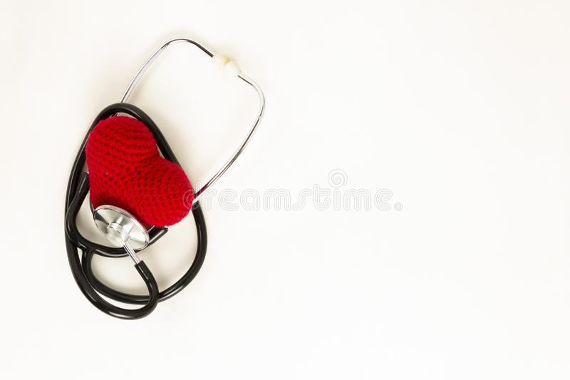 Heart health and prevention concept. Stethoscope and red heart of crochet on white isolated background with space for text stock images