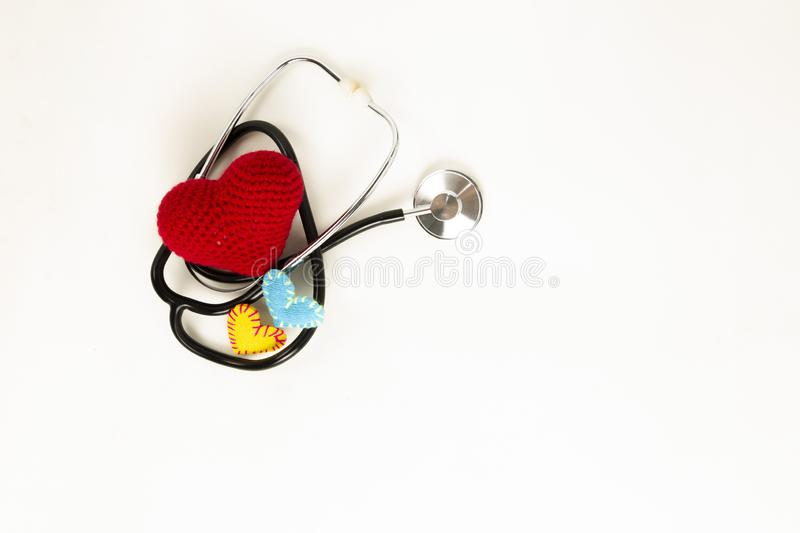 Heart health and prevention concept. Stethoscope and red heart of crochet on white isolated background with space for text.  royalty free stock images