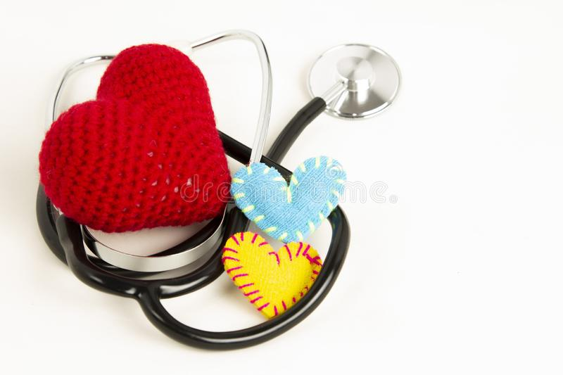 Heart health and prevention concept. Stethoscope and red heart of crochet on white isolated background with space for text.  stock photography