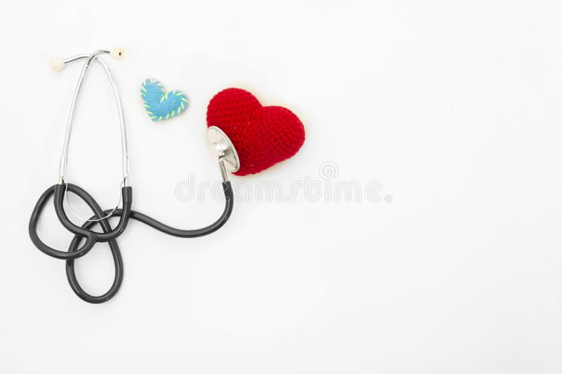 Heart health and prevention concept. Stethoscope and red heart of crochet on white isolated background with space for text.  royalty free stock image
