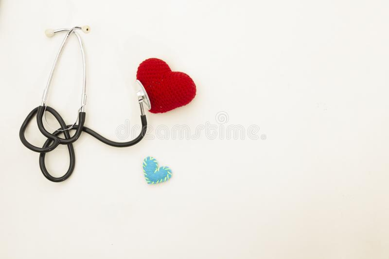 Heart health and prevention concept. Stethoscope and red heart of crochet on white isolated background with space for text.  royalty free stock photography