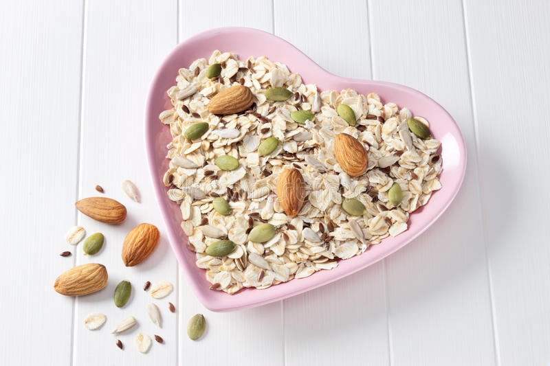 Cereal Granola Muesli Heart Food. A heart shaped bowl full of muesli, with oats, almonds and grains on a white background stock images