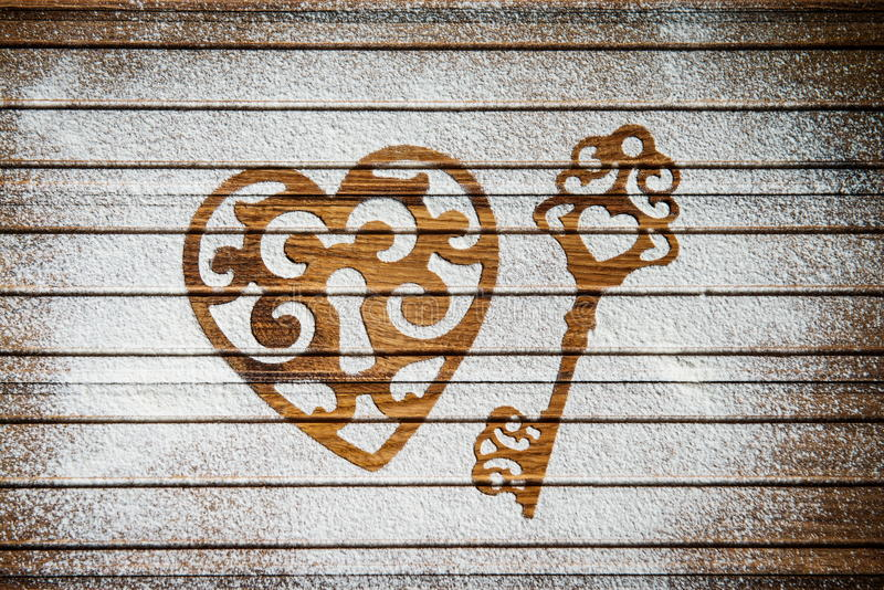 Heart and a key of the flour as a symbol of love on wooden background. Valentines day background. Vintage retro card. royalty free stock photography