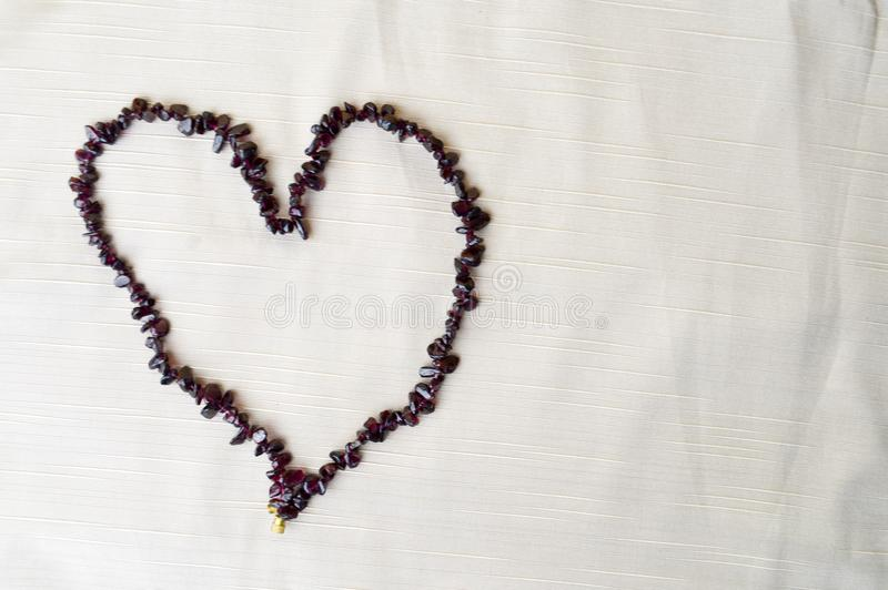 Heart laid out of female beautiful beads, necklaces of brown dark stones, amber against a background of beige fabric royalty free stock photos