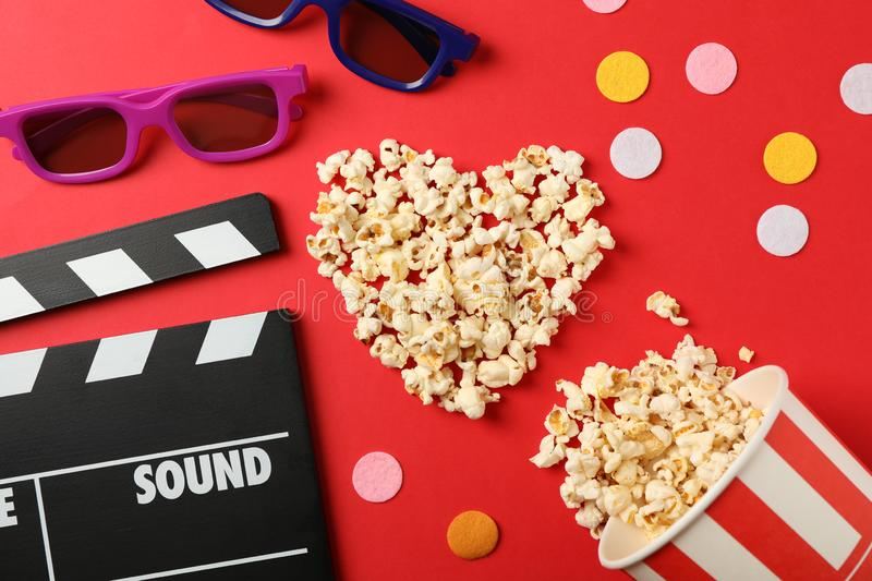 Heart laid out from popcorn, clapperboard, 3d glasses and bucket. On red background stock photography