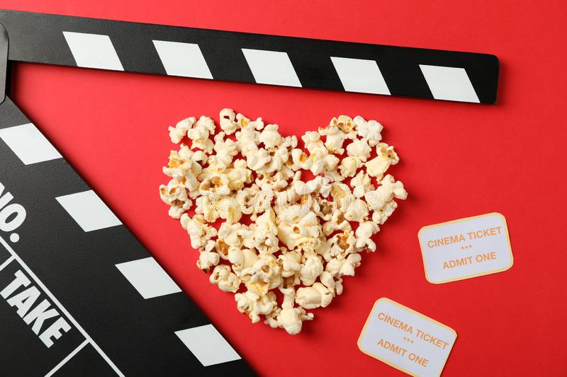 Heart laid out from popcorn, clapperboard and tickets on red background. Top view royalty free stock photo