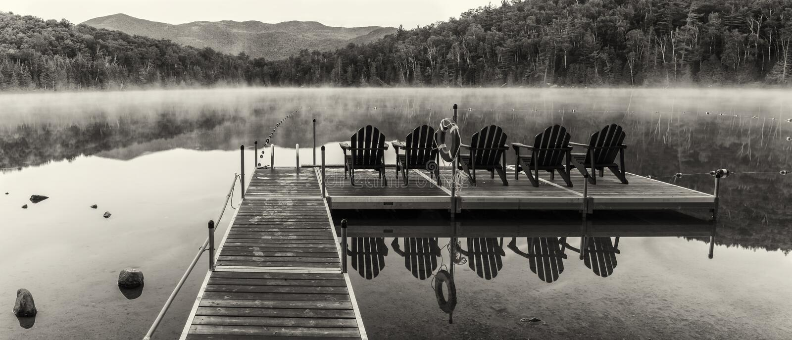 Heart Lake Dock Black and White Panorama. Black & white panorama of the Heart Lake dock on a misty morning in the High Peaks region of the Adirondack Mountains stock photography