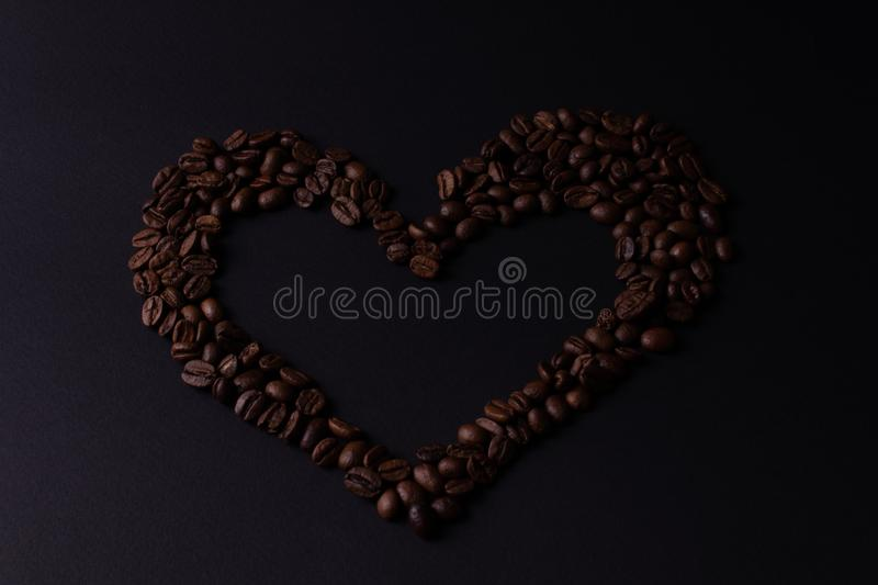 Heart lined with grains of coffee on a dark background top view royalty free stock photo