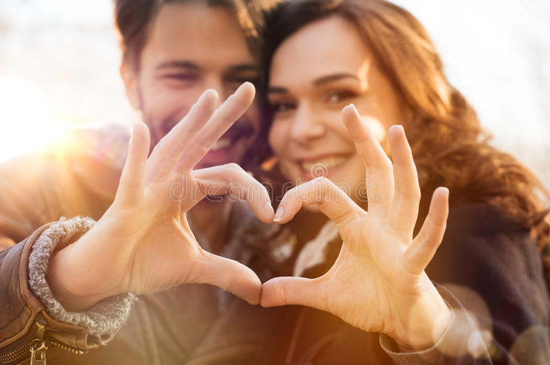 Heart and love. Closeup of couple making heart shape with hands royalty free stock images