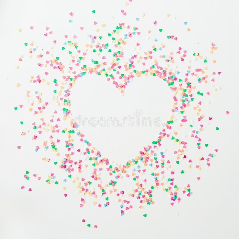 Heart love symbol made of colorful bright confetti on white background. Flat lay, top view copy space. stock images