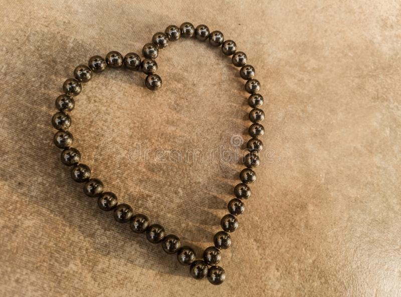 Heart of love symbol in magnetic ball bearings. Top view on tile background royalty free stock images