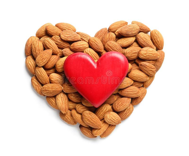 Heart made of almonds and decor on white, top view. Healthy diet stock photography