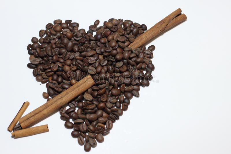 Heart made with beans of coffee. Cinnamon arrow crossing the heart as love symbol in a white background royalty free stock images