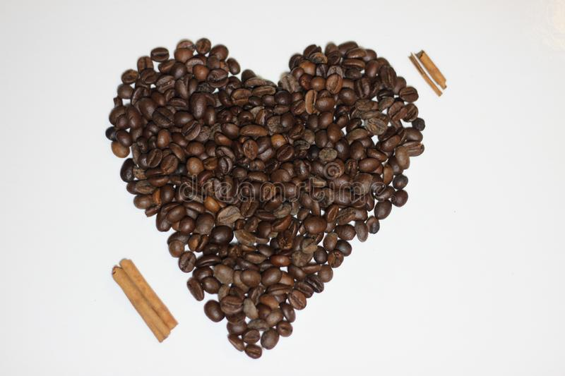 Heart made with beans of coffee. And cinnamon, heart as love symbol in a white background stock photo