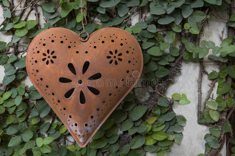 A heart made of beautiful copper metal hangs on green wall stock image