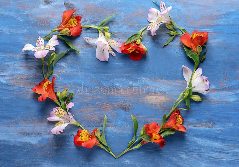 Heart made of beautiful flowers on color wooden background royalty free stock image