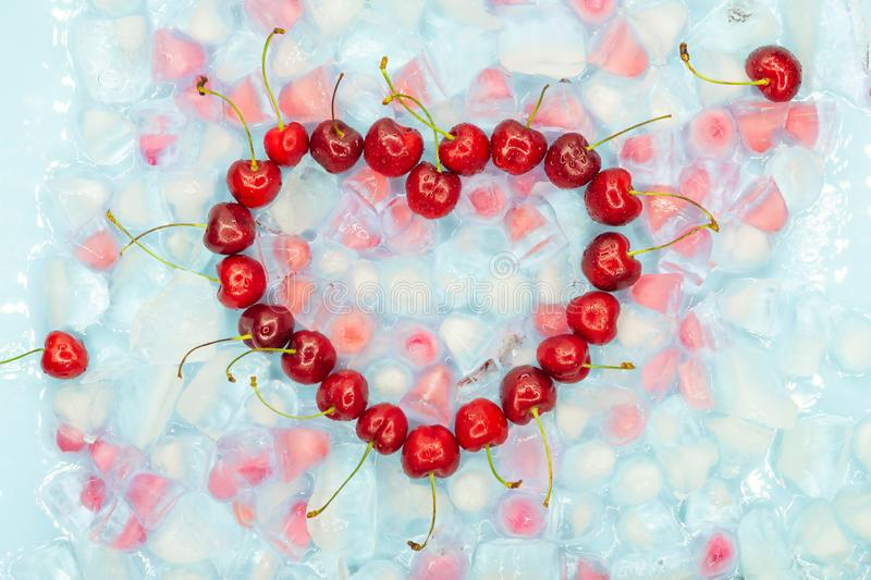 Heart made of cherries against the background of transparent and pink ice cubes with copy space. Top view. Fresh summer romantic stock image