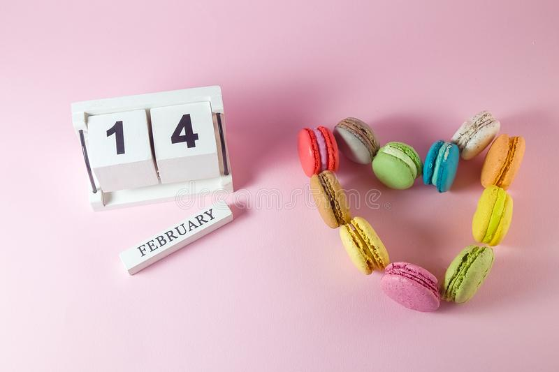 Heart made of colorful macarons and wooden calendar. stock photo