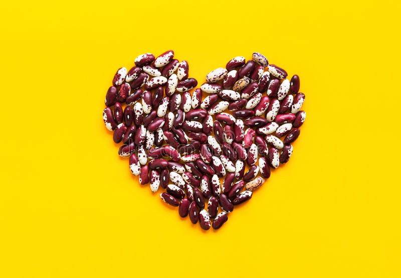 Heart made from dry uncooked red and white speckled beans on bright yellow background. Creative food art poster. Health plant based meatless diet wholefoods stock photography