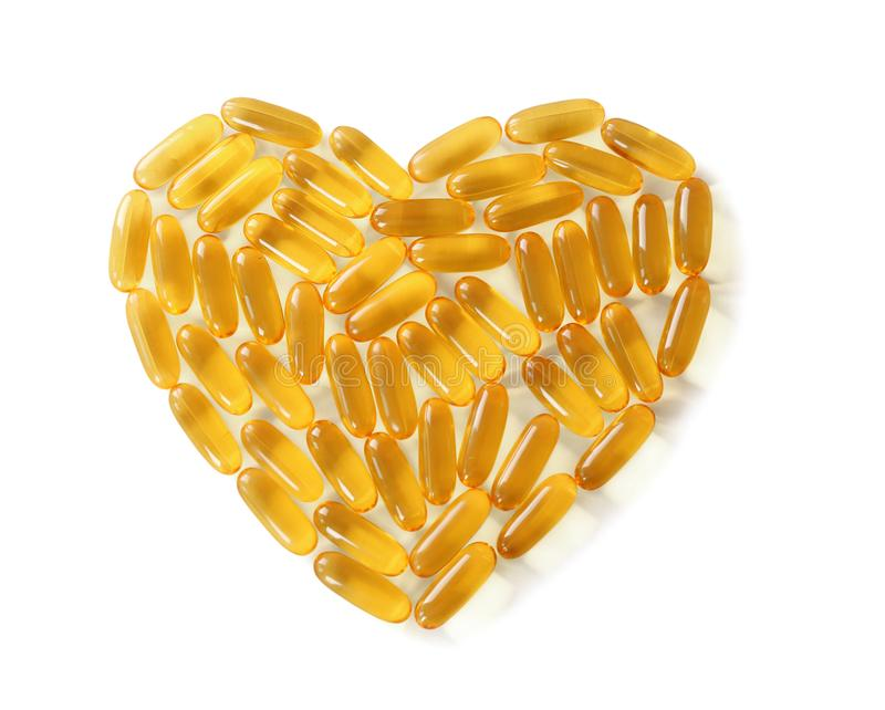Heart made of fish oil capsules. On white background royalty free stock photography